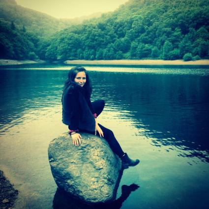 Portrait photograph of Karis sitting on a rock, on the edge of a lake, in Scotland