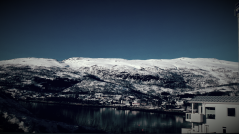 Landscape scene in Norway picturing a house, mountain and lake