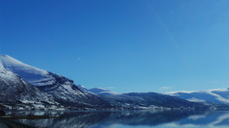 Photograph in Norway picturing a snowy mountain and blue lake